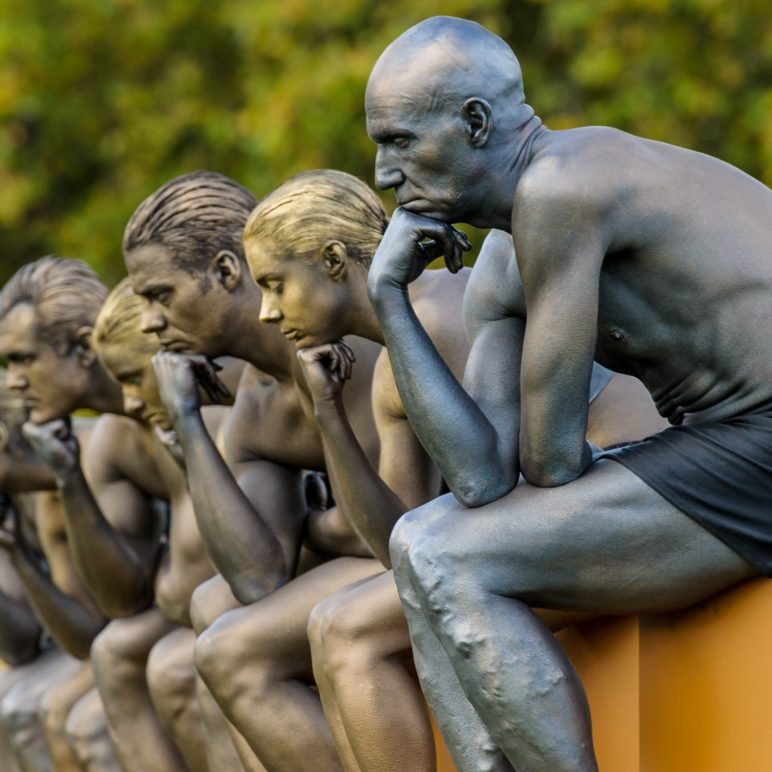 Nine models pose as Rodin's The Thinker